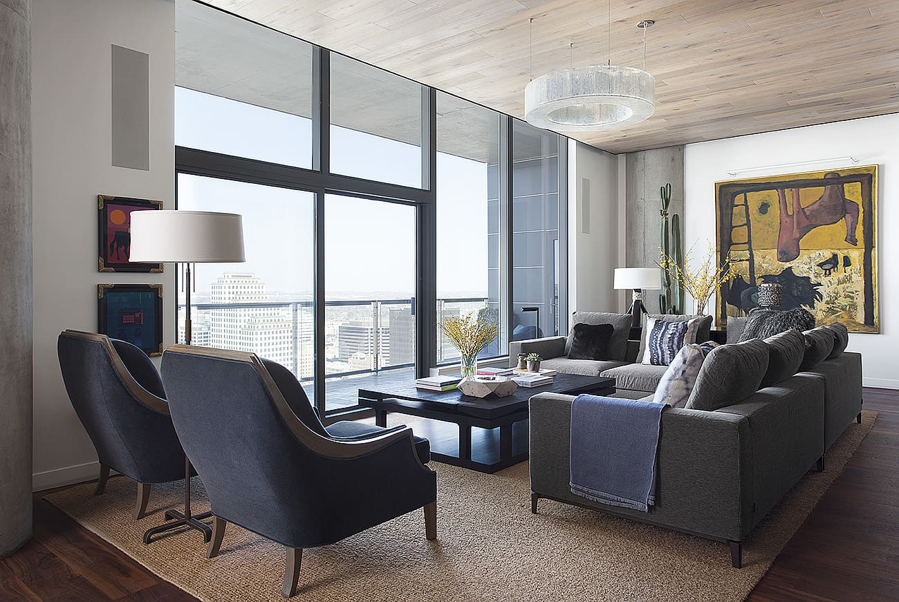 Large living room in Texas condo with area rug, two sofas and two accent chairs.