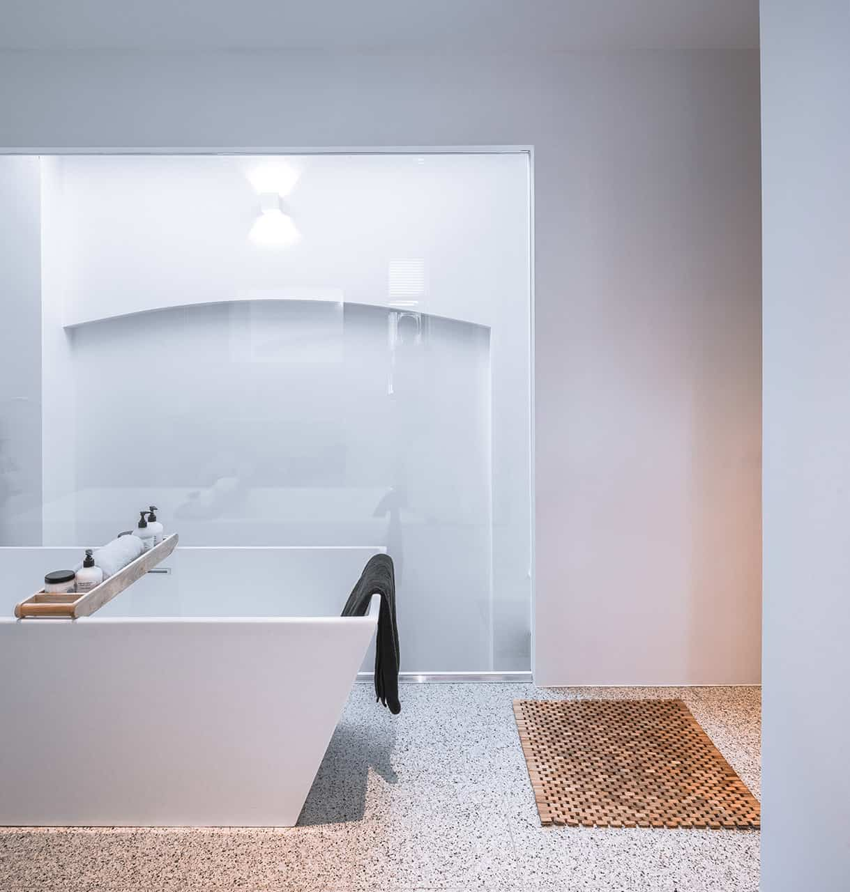Freestanding white modern bathtub agains large picture window.