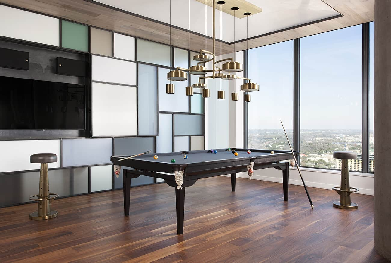 Large game room with stylish black billiards pool set on the hardwood flooring and is lighted by stunning ceiling lights.