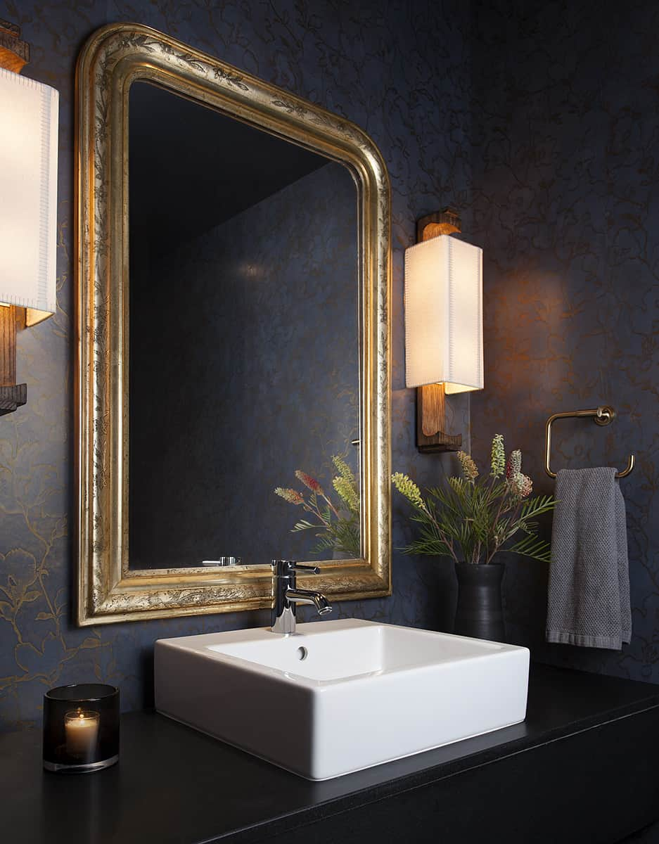 Beautiful powder room with white sink, gold framed mirror and dark walls in Texas condo