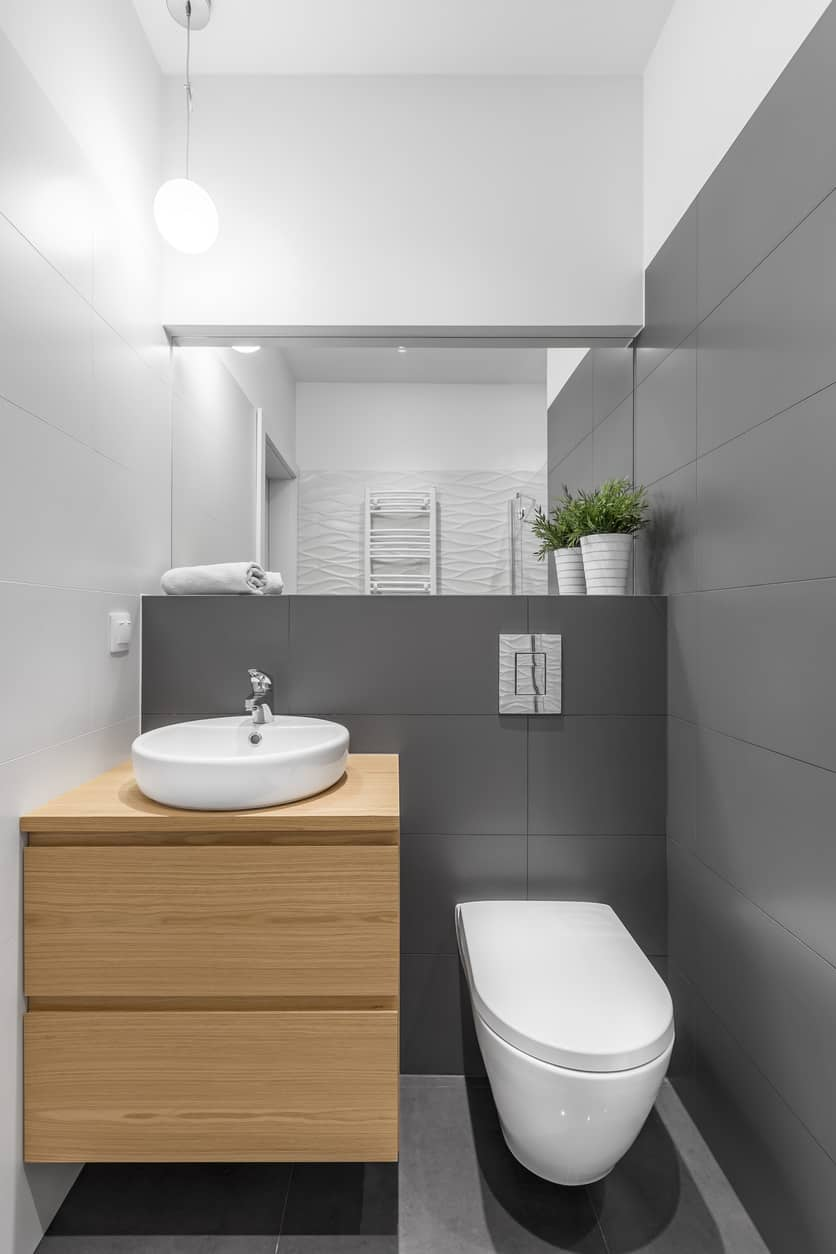 Minimalist powder room with gray and white color tones and white vessel sink.