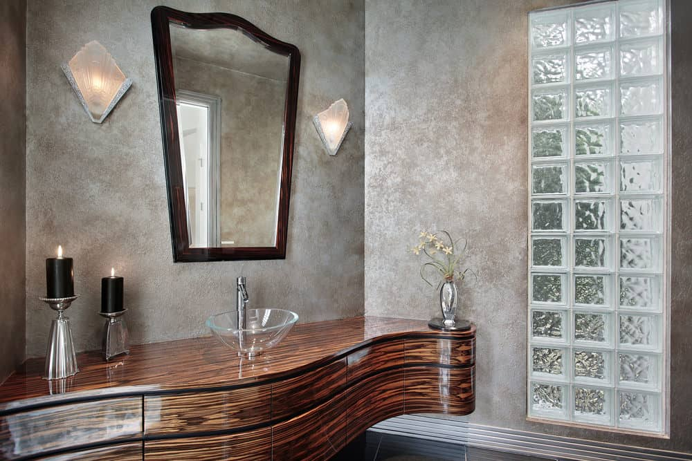 Powder room with gray wall finish, vessel glass sink, and wall lighting.
