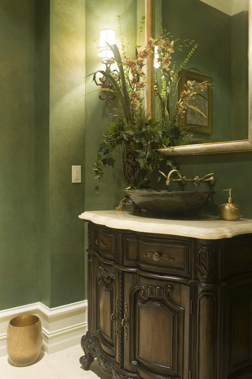 Powder room with green walls, wall lighting, and single vessel sink.