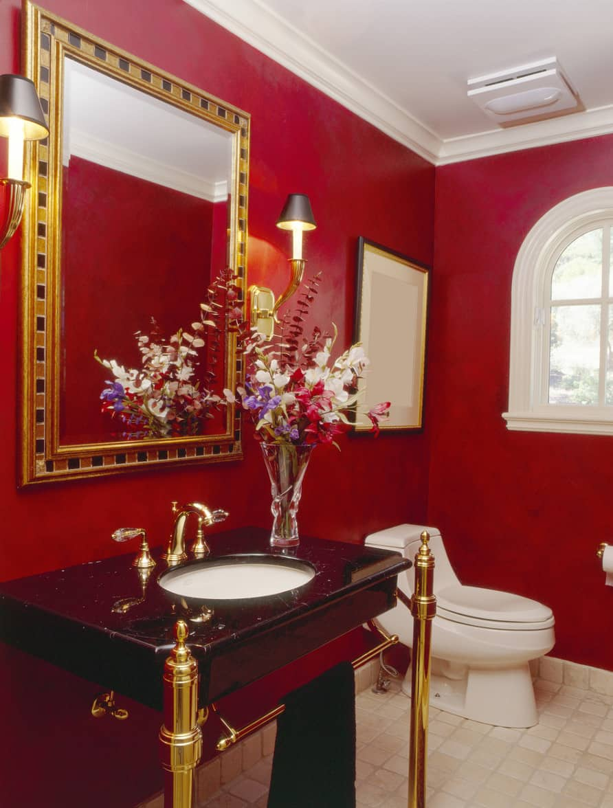 Powder room with red walls, tiled floor, double wall lighting, and undermount sink. Gold-rimmed mirror and vanity legs add an ornateness to this design.