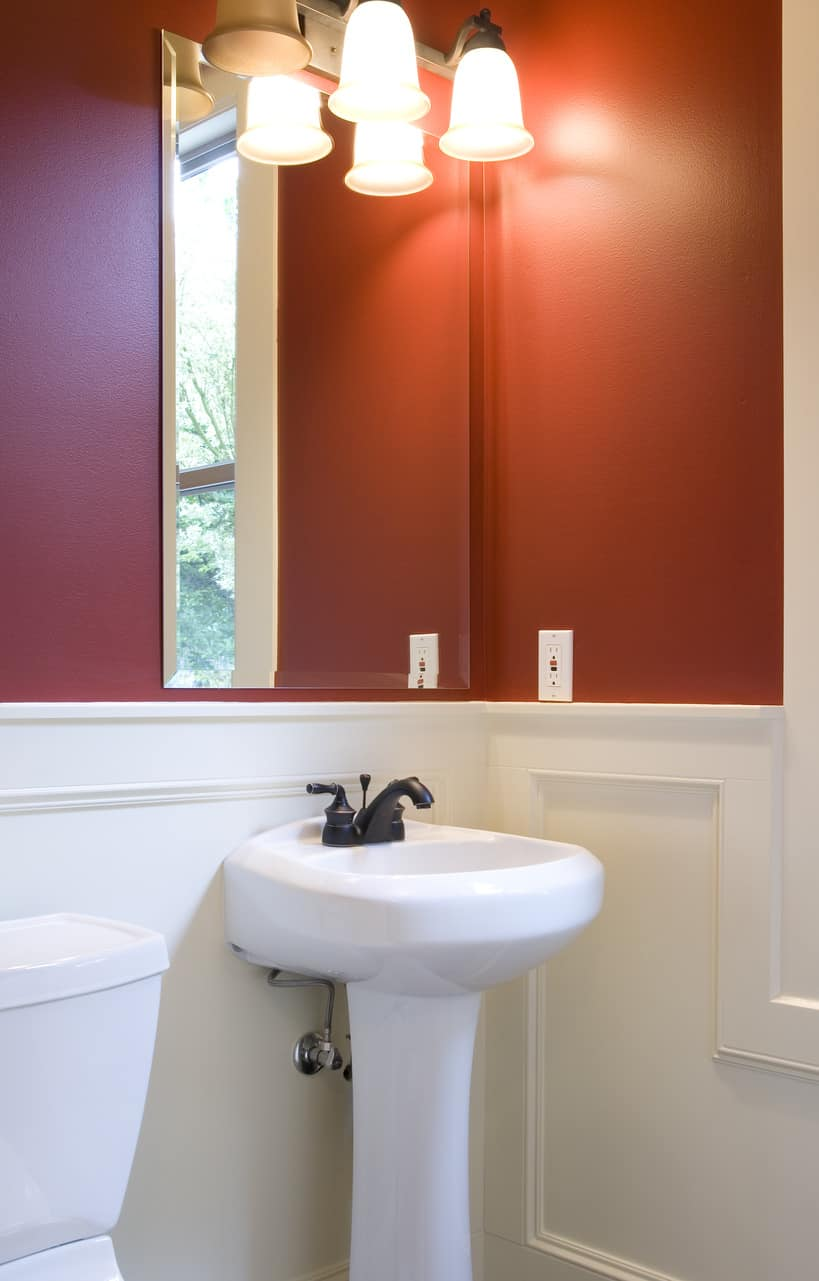 small powder room with white and red walls, wall lighting, and pedestal sink.