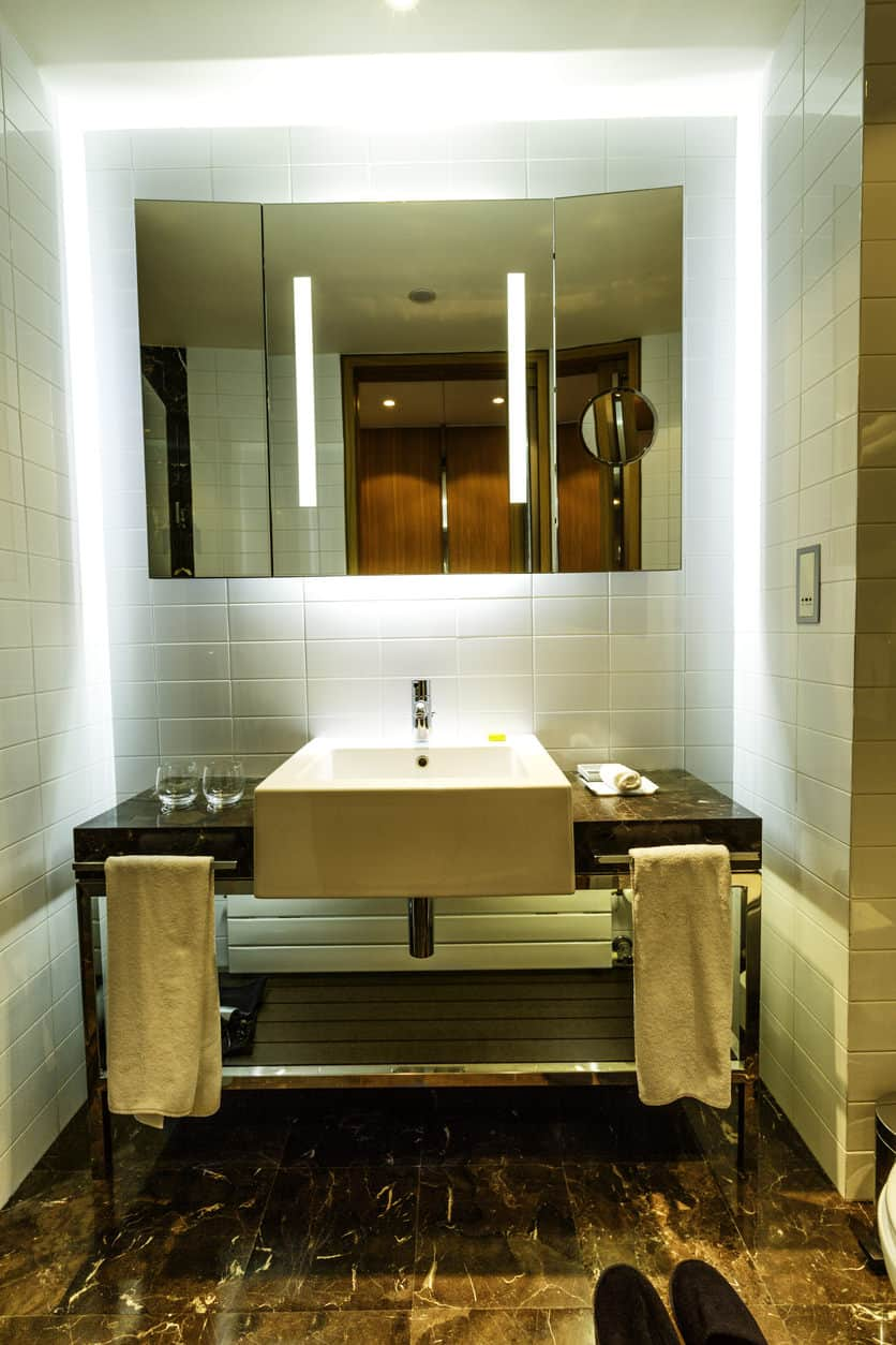 Powder room with pedestal sink, double background lighting, two towel holders, and tiled wall.