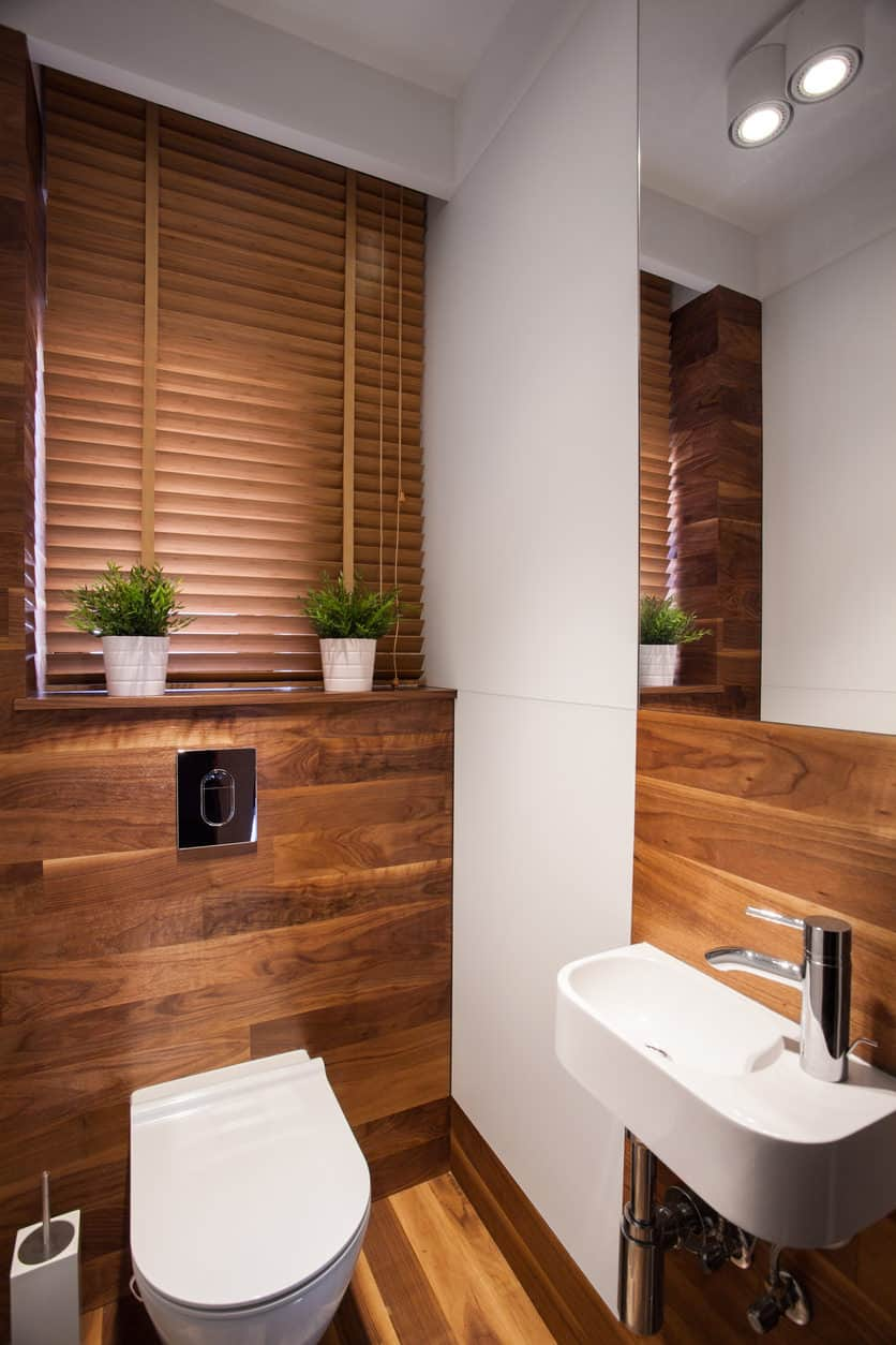 Powder room with wooden finish, brown blinds, toilet with automatic flush system, white sink, and ceiling lights.