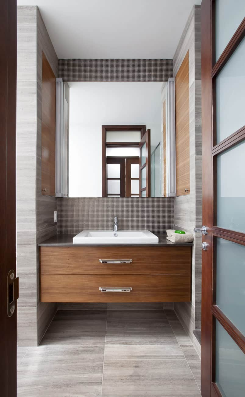 Powder room with white and gray wall hues, half-body mirror, single white sink and grayish tiles.