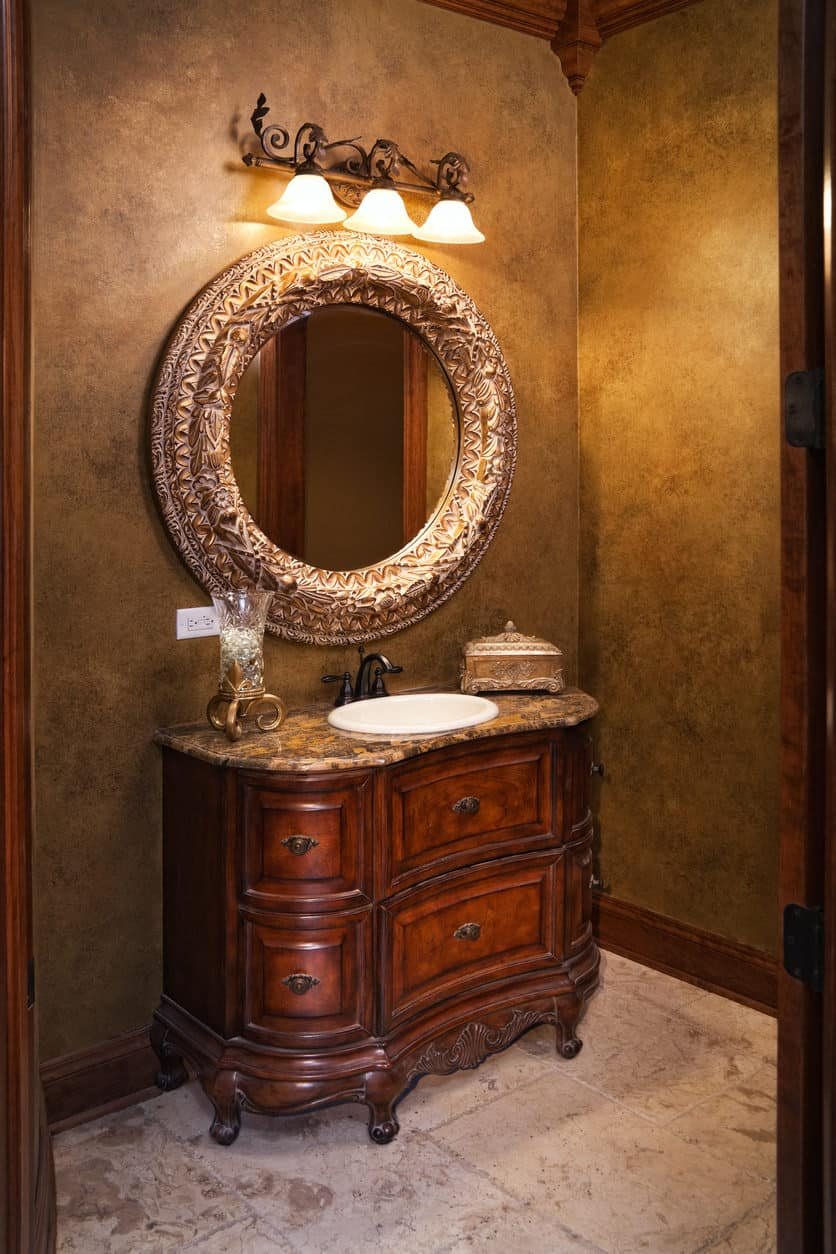 Vintage-looking powder room with three-receptacle wall lighting, round mirror, and undermount sink.