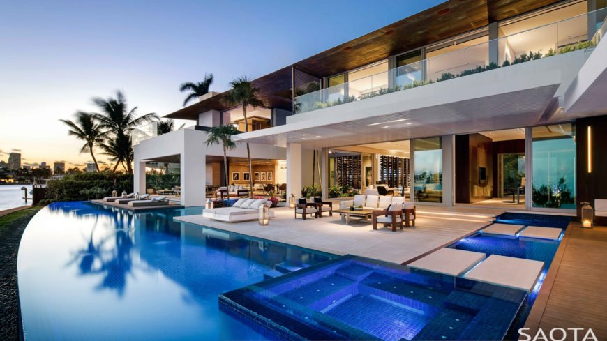 This luxurious home features a luxurious infinity pool with multiple loungers and a patio area on the side.