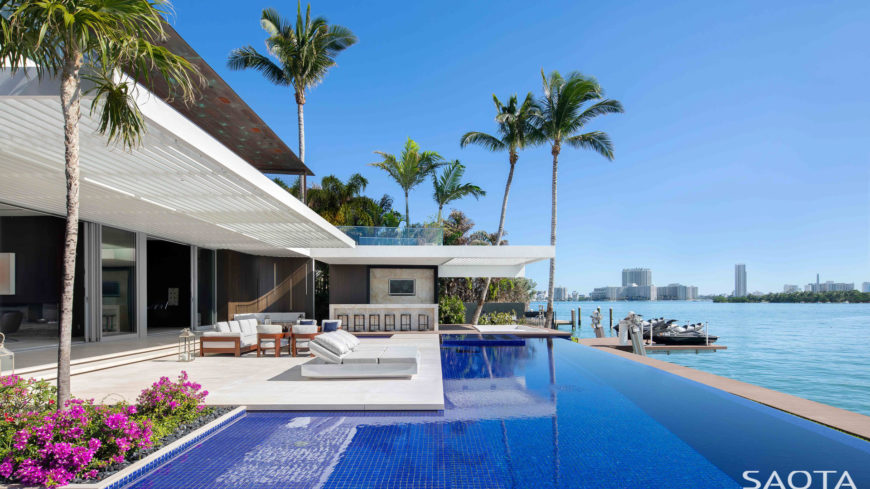 Stunning infinity pool featuring a set of loungers and a patio area on the side.