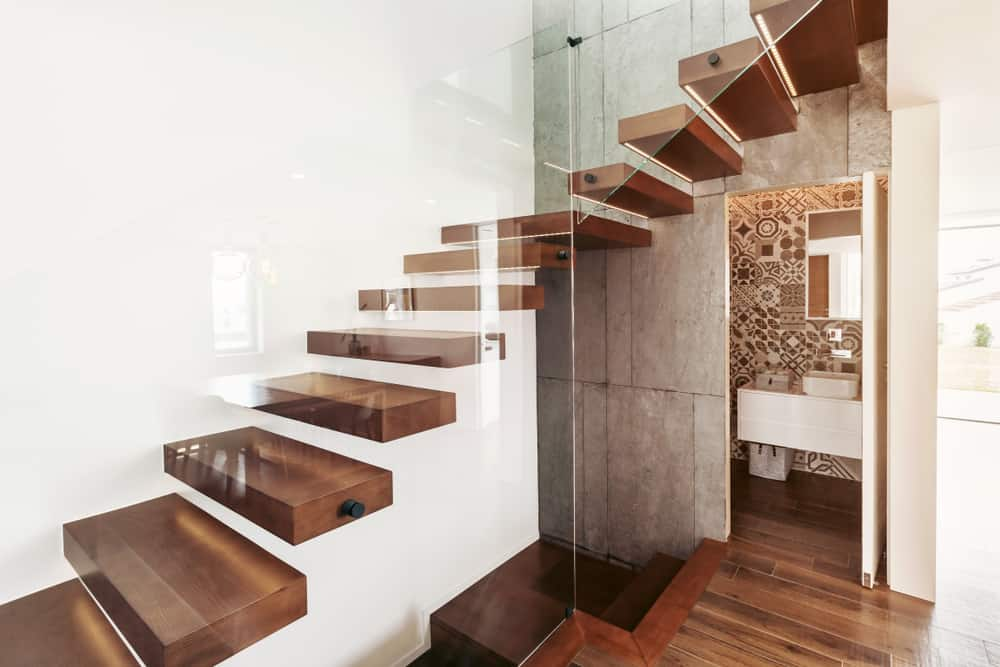 Staircase as bridge floating above bathroom entrance.