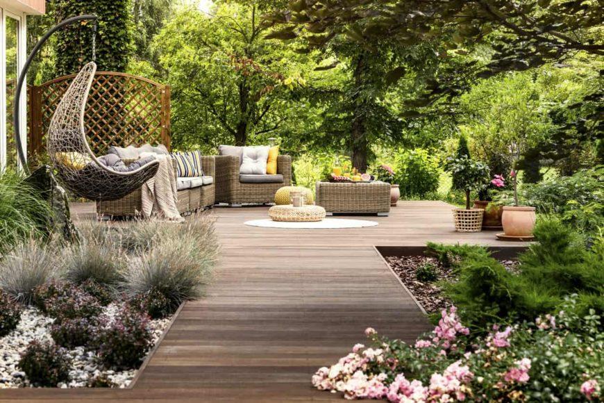 Stunning backyard deck with hammock, garden and trees.
