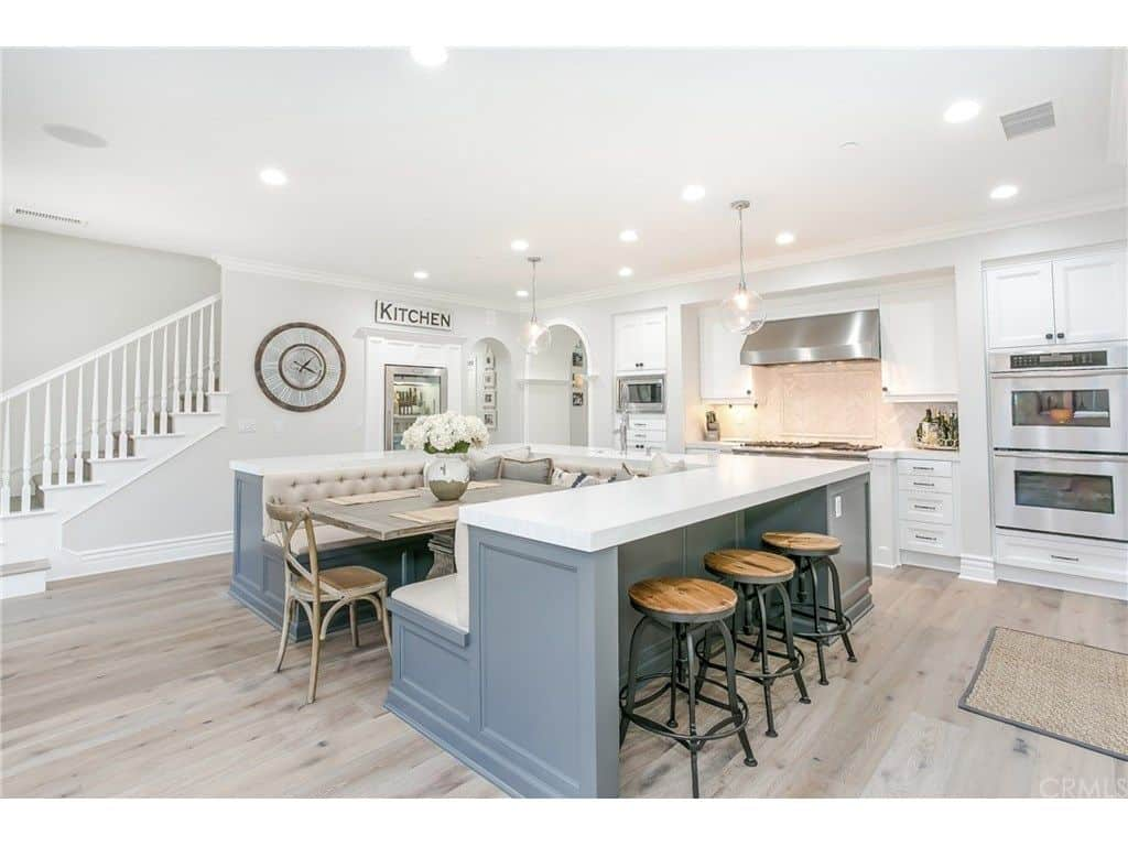 Large white kitchen with u-shaped island that includes a built-in dining table and bench seating