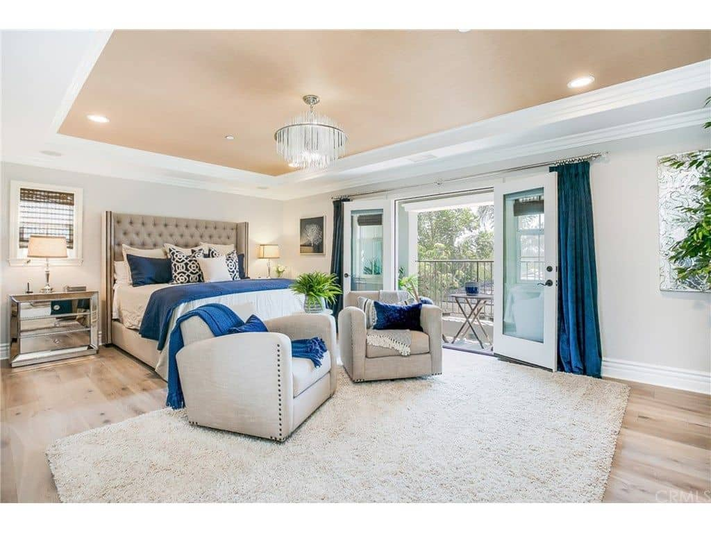 Tamra Judge house - tasteful primary bedroom with tray ceiling, light wood flooring, balcony and sitting area.