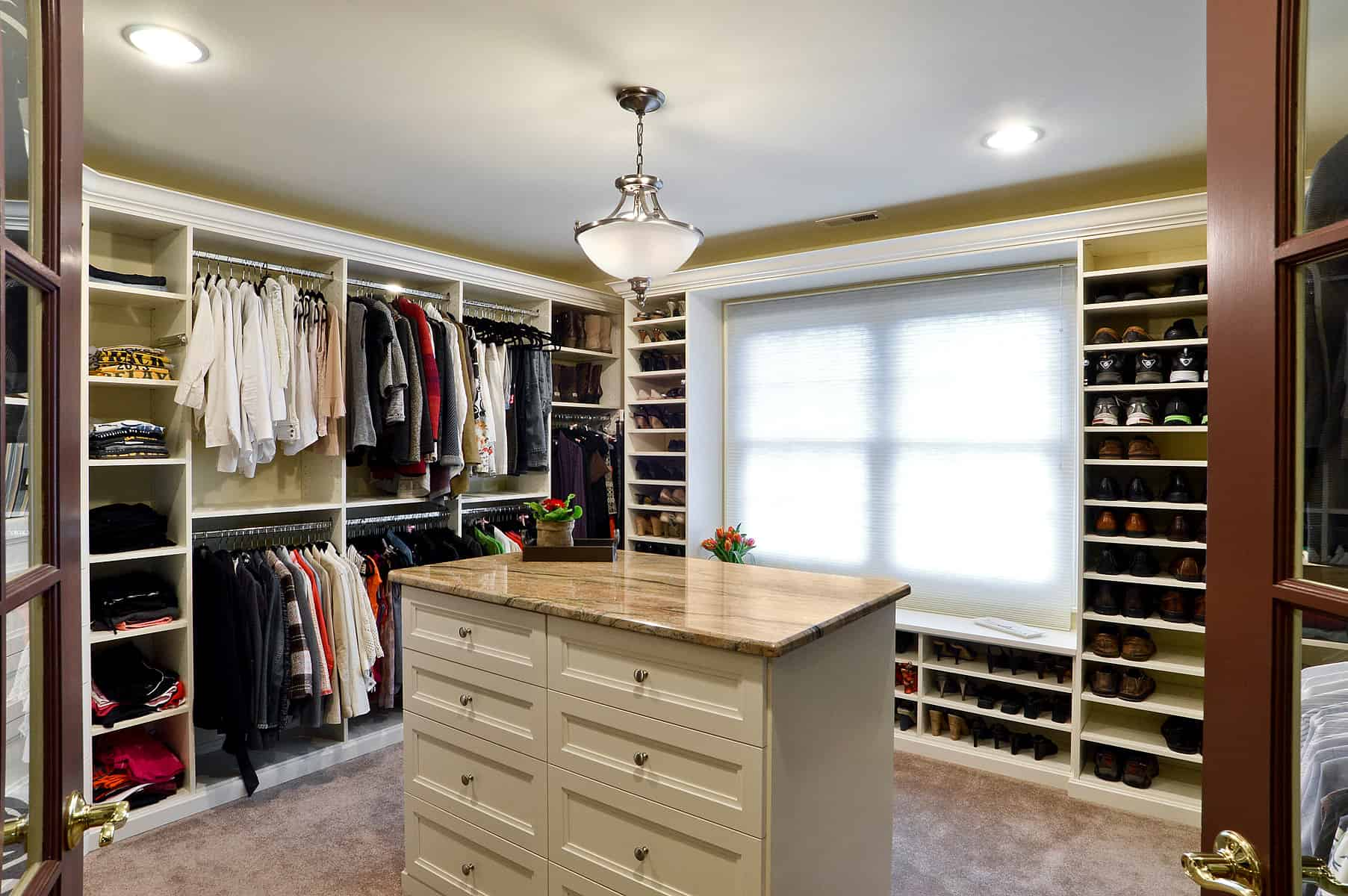 Such a grand walk-in closet can surely house all the apparels and accessories of all the family members. We see an entire wall dedicated to shoe storage while there is also a window seat for additional functionality.
