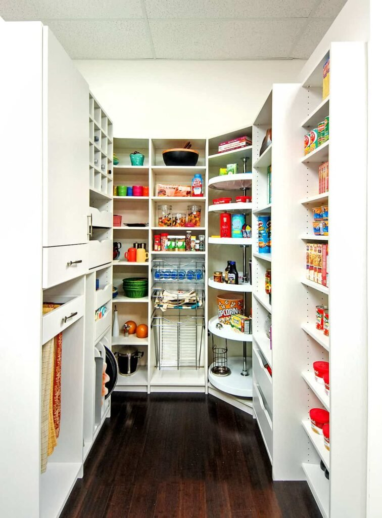 A closet pantry with white cabinetry and shelves along with a hardwood flooring.