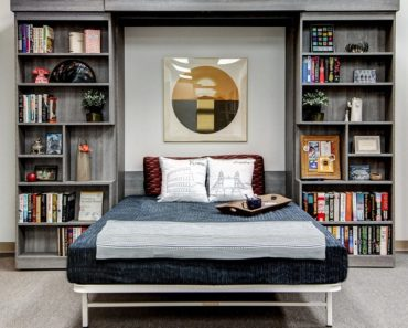 Wall bed set up as bed with bookshelves on both sides.