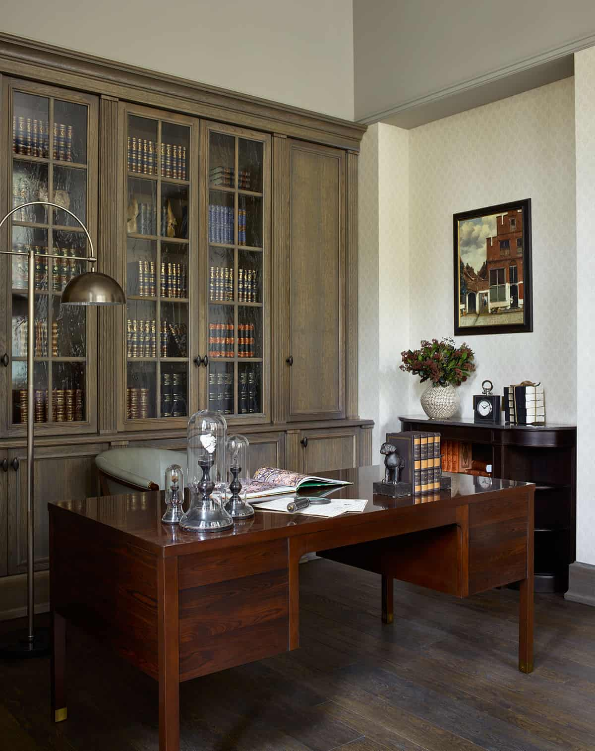 Home office featuring hardwood flooring and an elegant office desk surrounded by classy walls.
