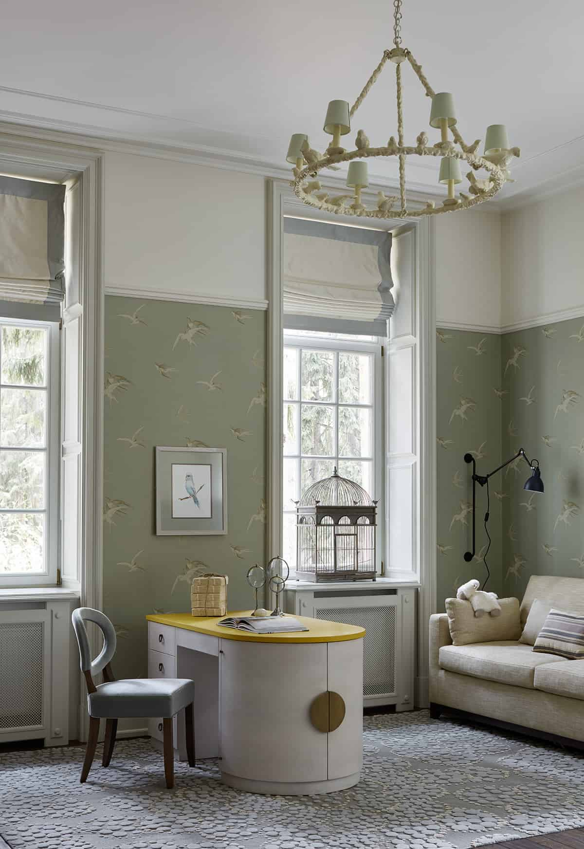 This home office features elegant walls and a luxurious chandelier. The room also features its own sitting area.