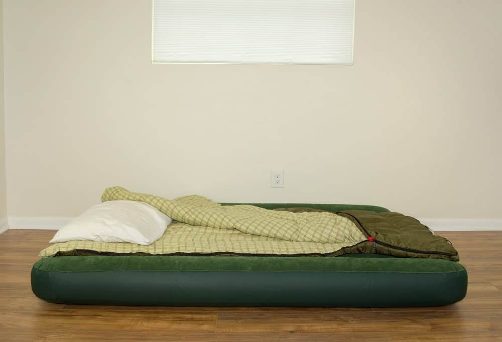 Air mattress on the floor with pillow and sleeping bag.