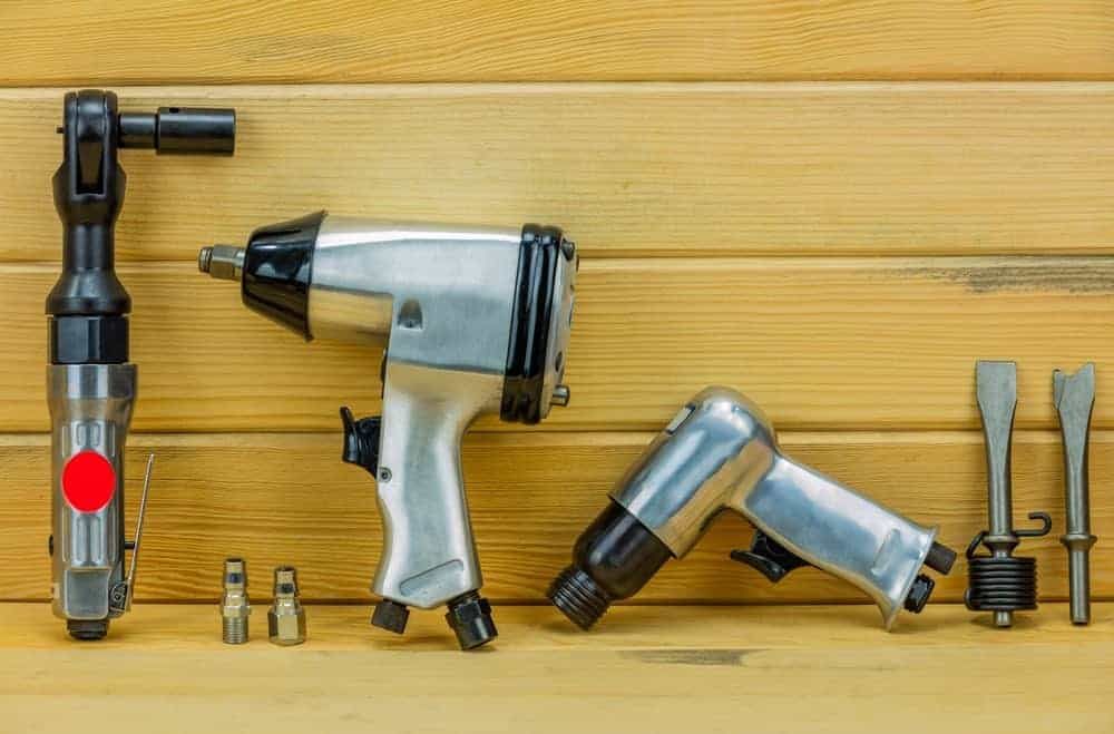 Different types of air tools on wooden background.