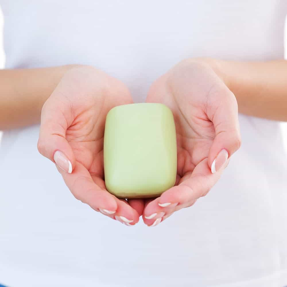 A lady is holding a bar of soap.