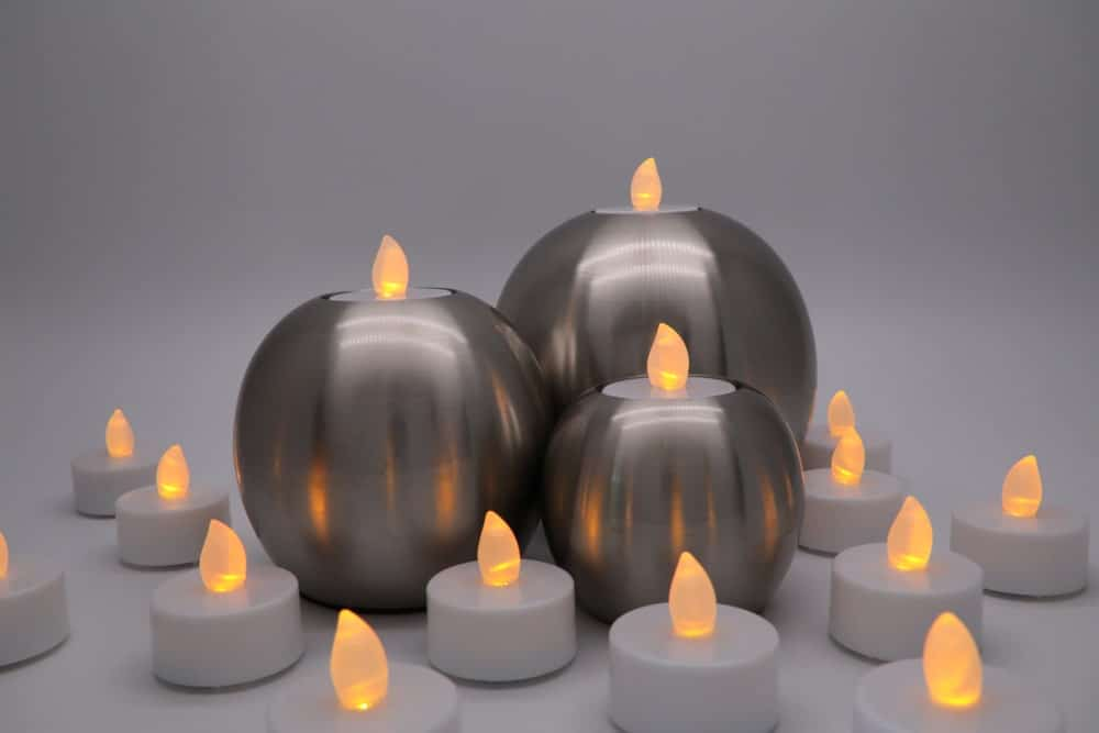 Battery-operated candles in stainless steel containers.