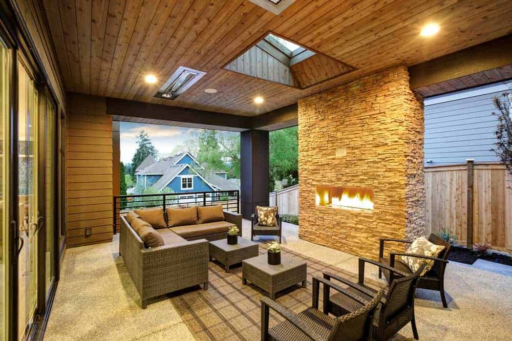 This is an outdoor covered patio with stone fireplace, a beadboard ceiling with skylight, rattan armchairs, sofa and ottomans overlooking the expansive backyard.