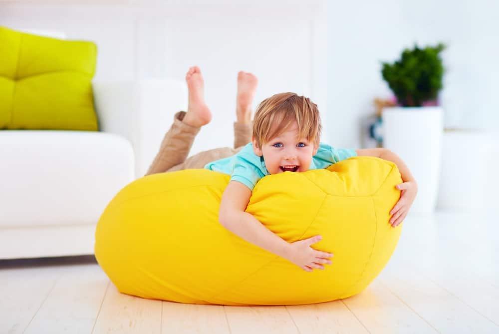 A boy is feeling comfortable on a yellow bean bag.