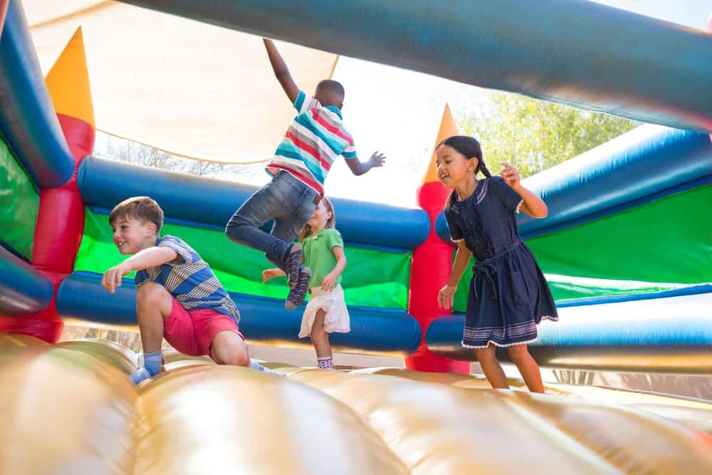 Four kids are having a great time inside playing around inside an inflatable castle.
