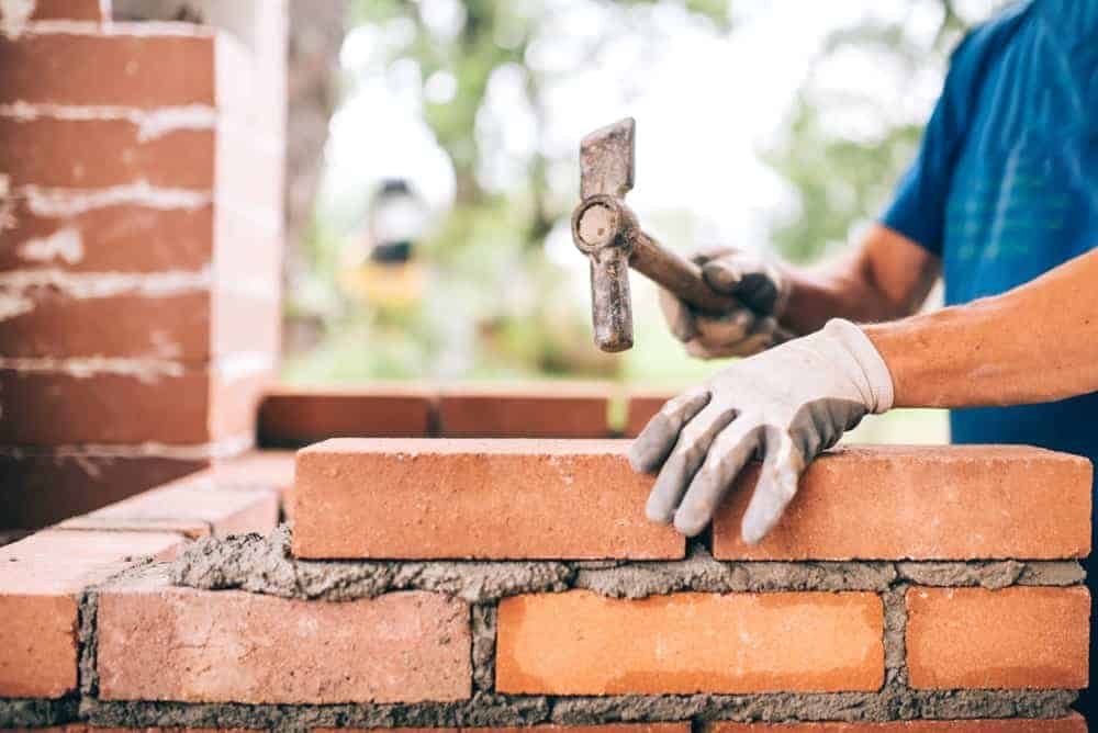 A worker uses a brick hammer for laying bricks.