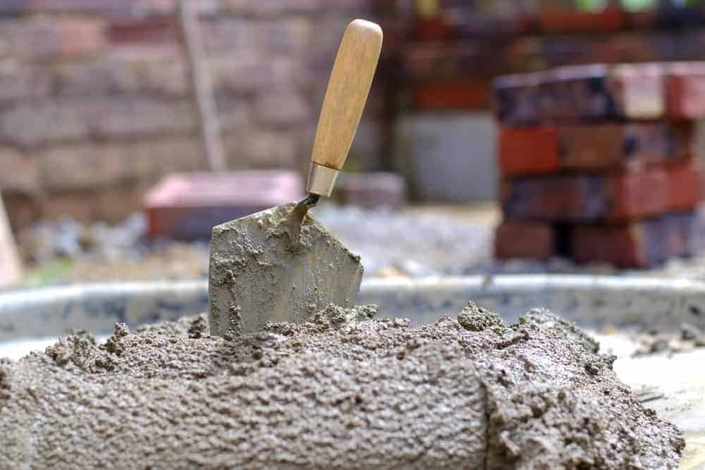 A brick trowel is half-buried in cement.