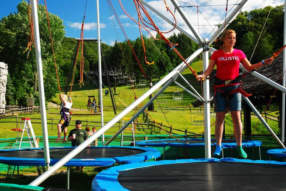 A lady has some safety ropes on as she prepares to experience the bungee trampoline.