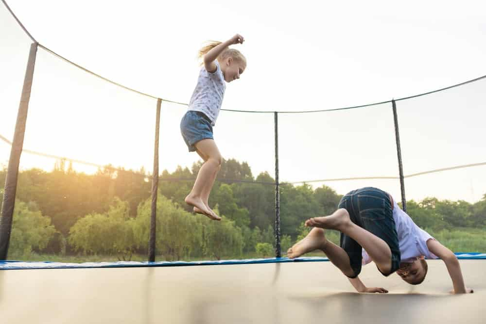 Two children are playing in a caged trampoline.