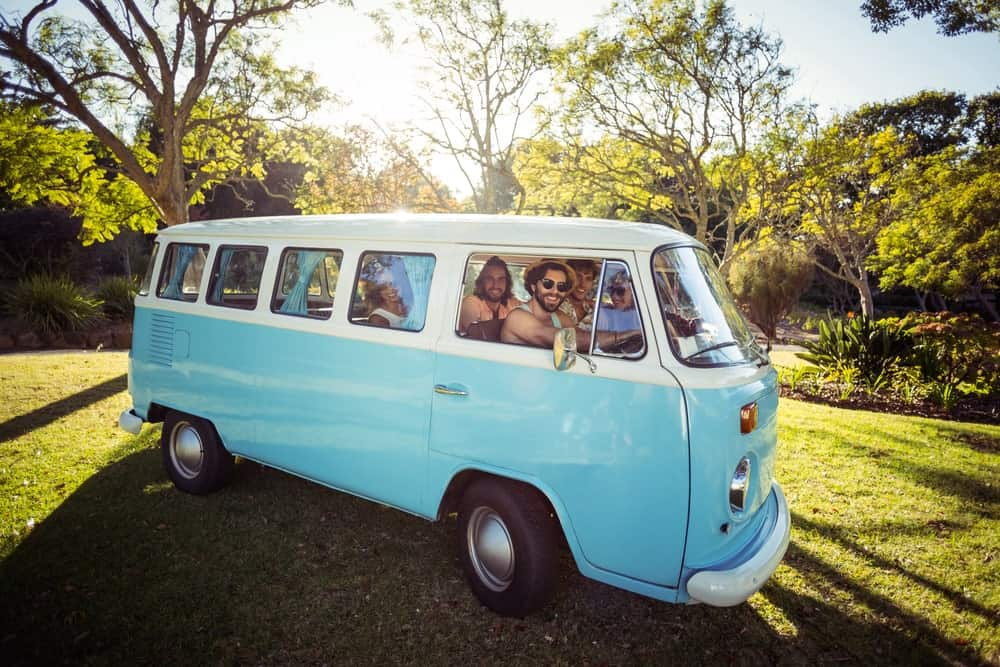 A group of friends in a campervan taking shelter under some trees.
