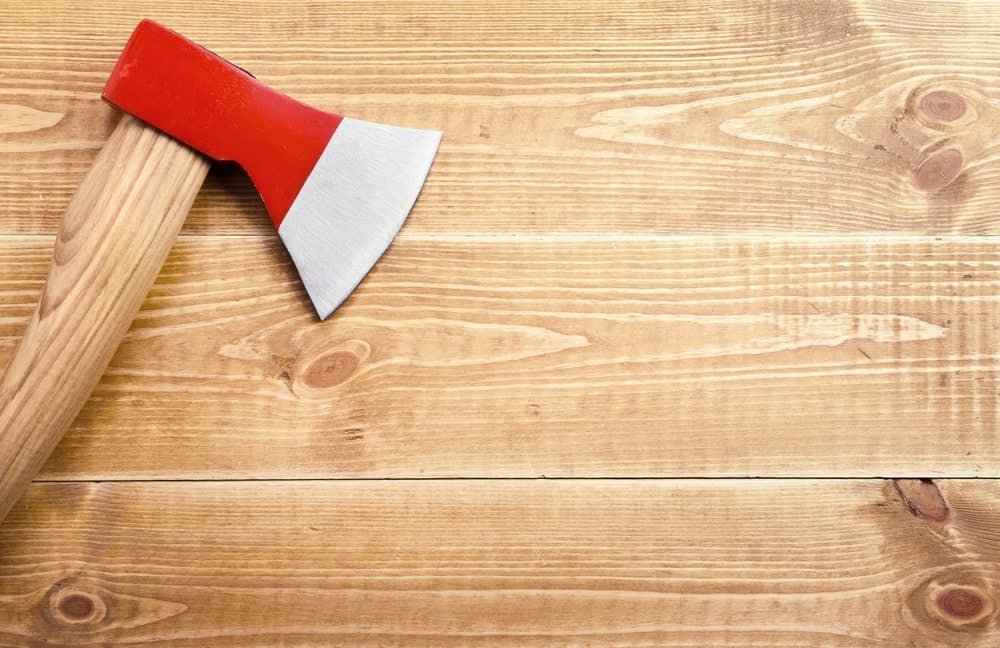 Carpenter's Ax on wooden background.
