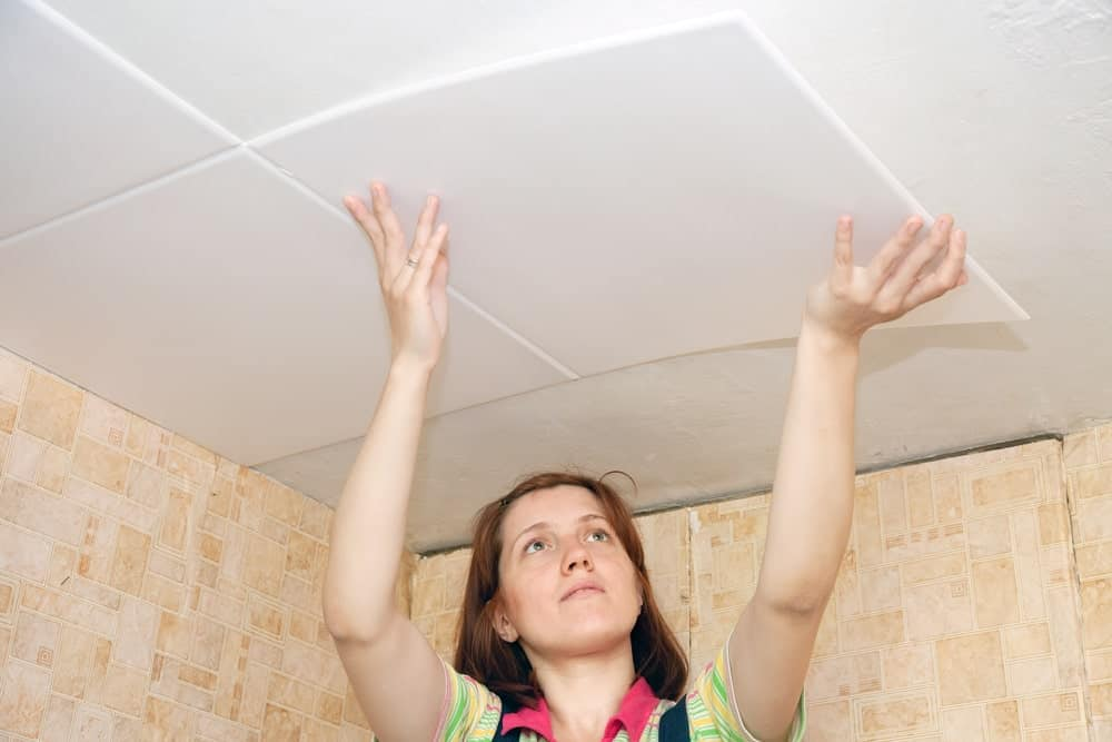 A woman is pictured gluing tiles on the ceiling.