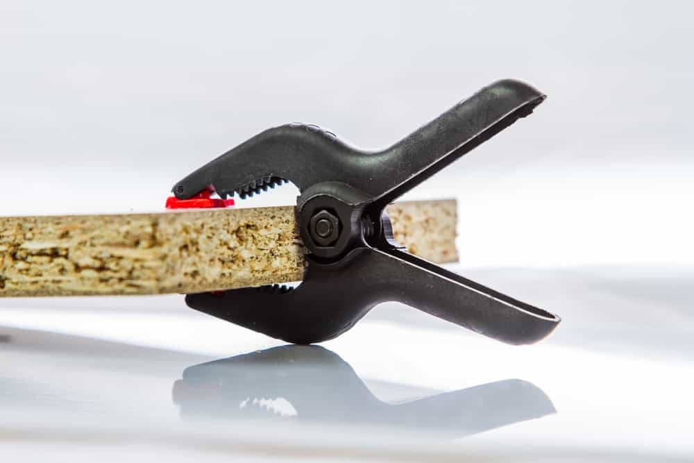 A clamp used to hold a piece of wood on white background.
