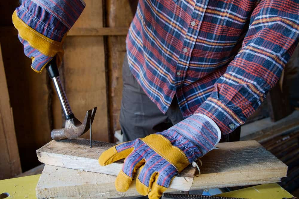 Worker using a claw hammer to remove a piece of nail from the wood.