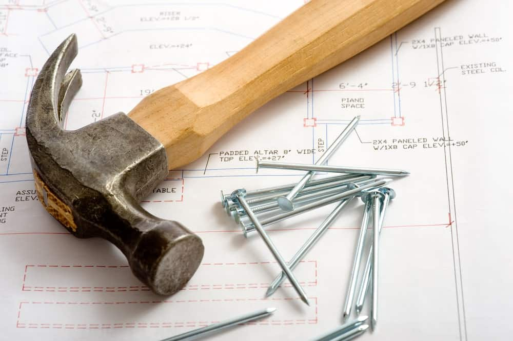 A claw hammer and nails on top of a paper with diagrams.