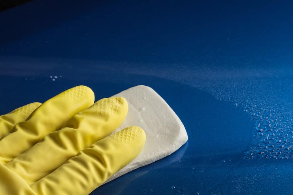 Gloved hand on clay bar on the surface of a car.