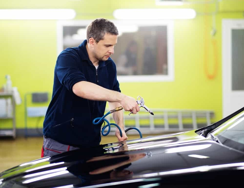 Mechanic using a compressed air for drying the washed car.