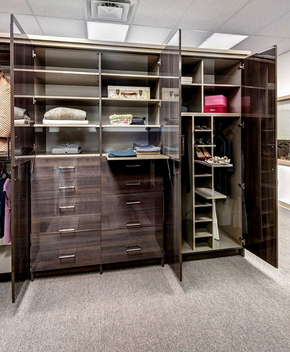 Modern closet boasting a carpet flooring, classy cabinetry and a gorgeous lighting and ceiling.