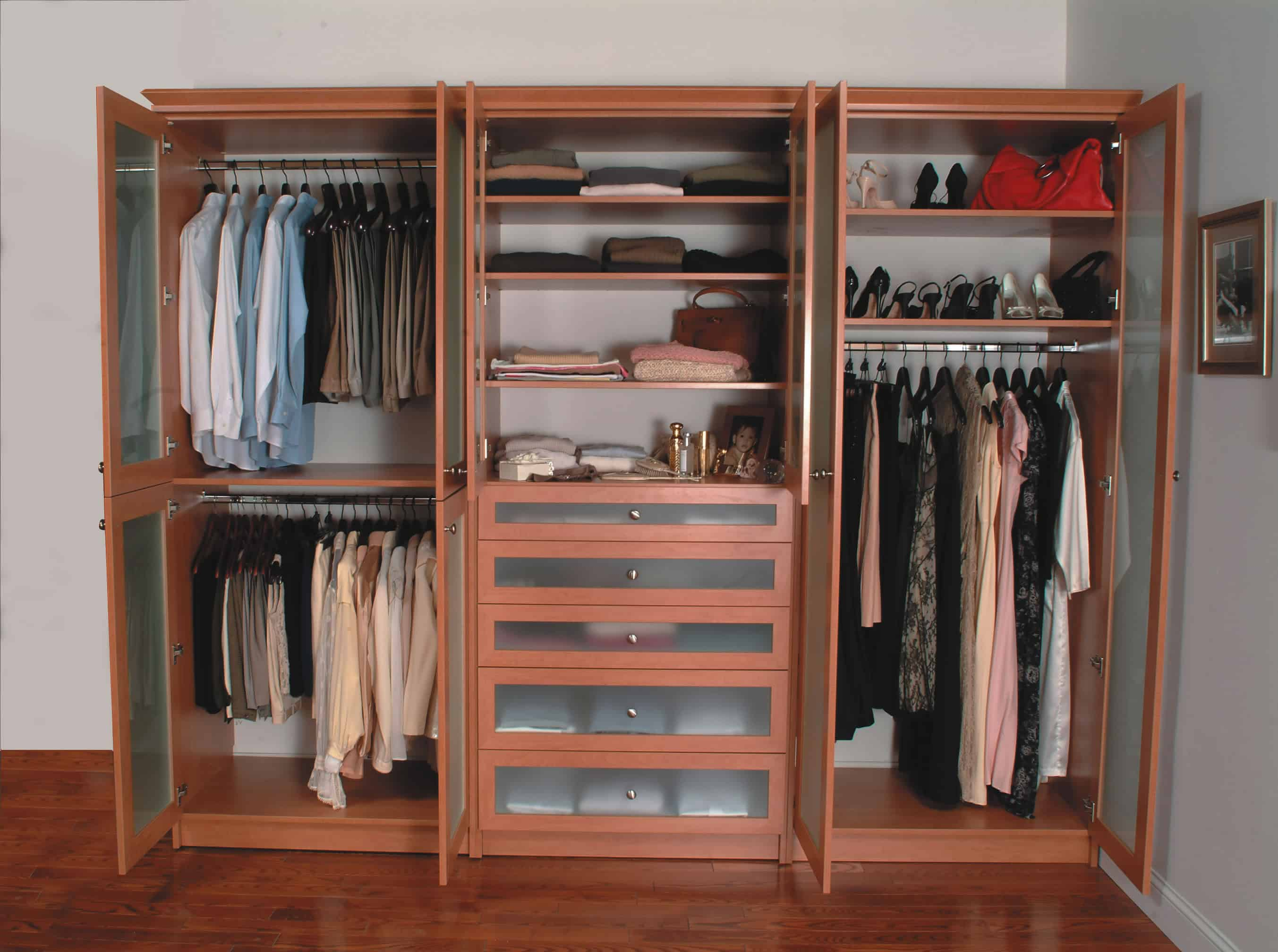 This modern women's clothing features beige finished cabinetry and reddish hardwood flooring along with white walls.
