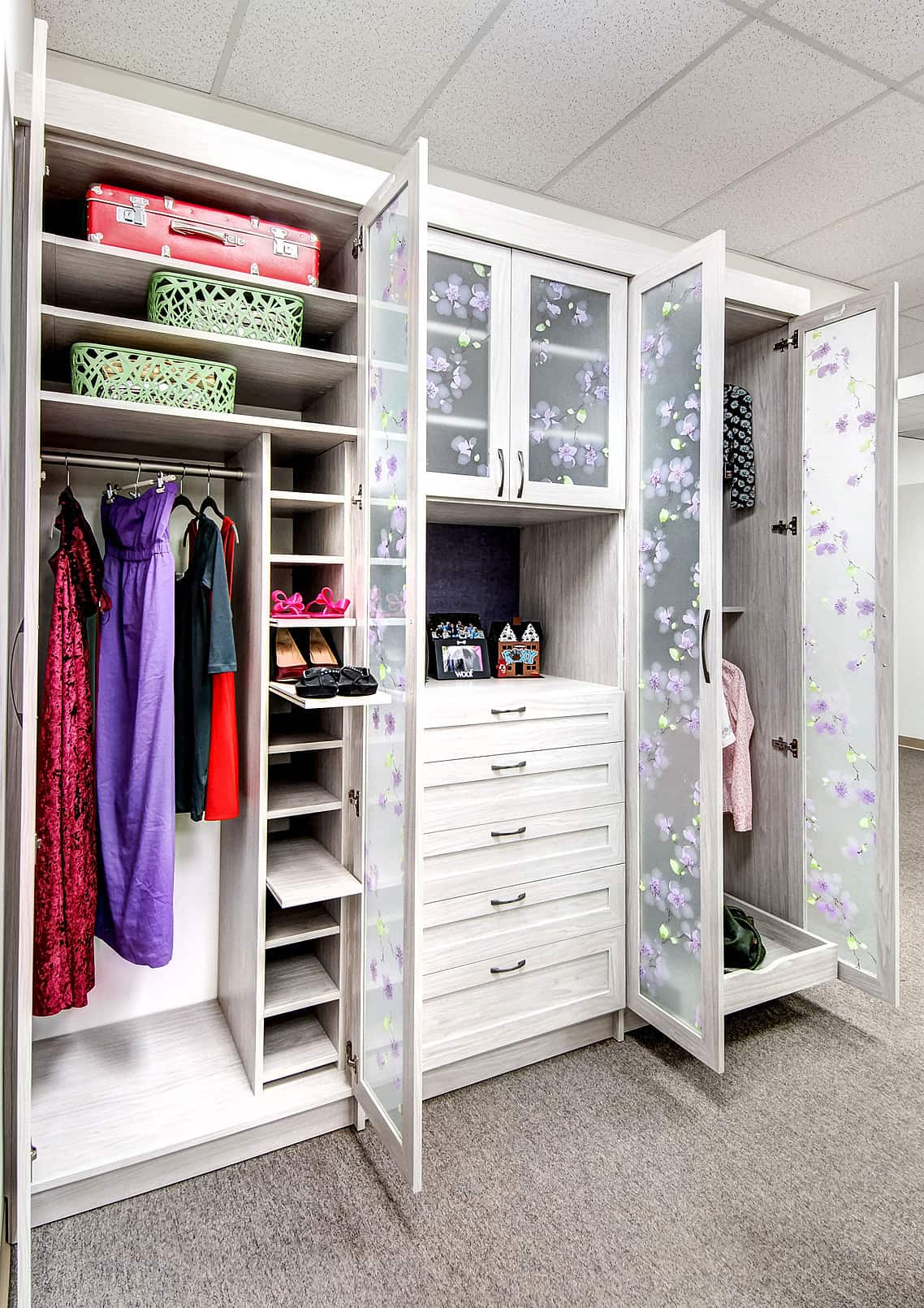 Women's bedroom closet featuring a carpet flooring and white finished cabinetry.