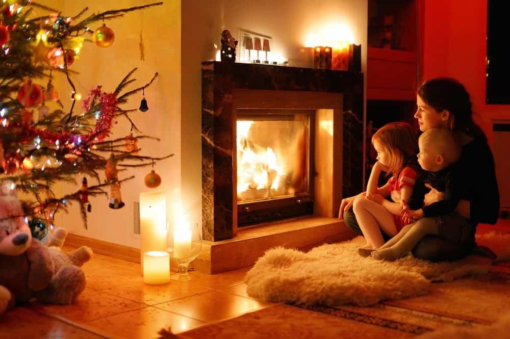 A young mother with her children are warming up in front of a fireplace.