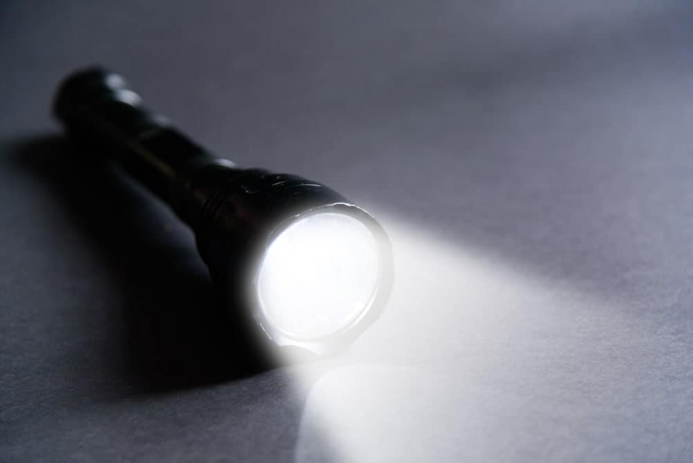 Beaming flashlight on gray background.