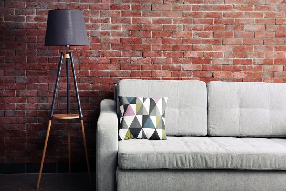Floor lamp beside a sofa in a room with brick walls.