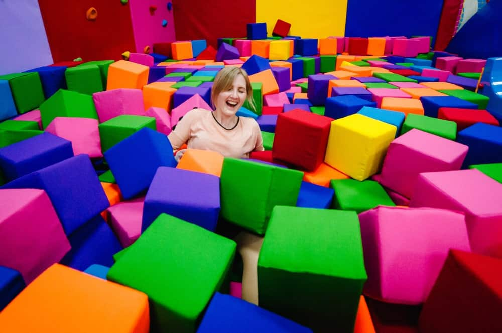 A teenage girl is trying to get up after she jumped right into the foam pit.